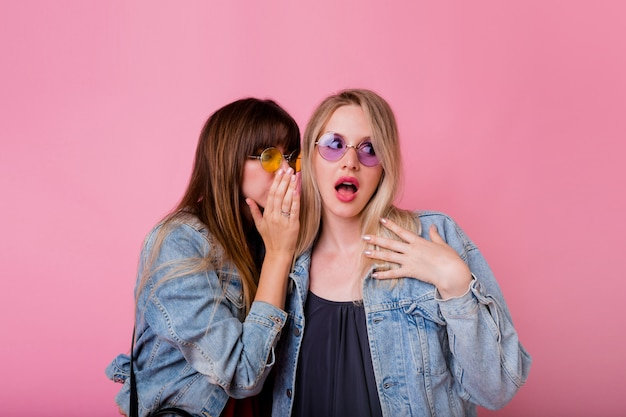 Two emotional women gossip up on pink wall Free Photo