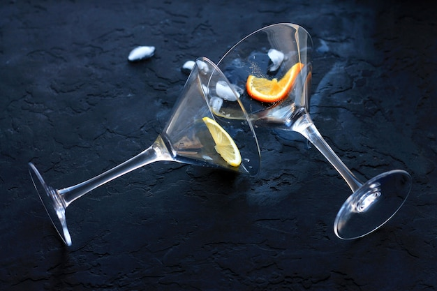 Two empty cocktail glasses will fall overturned out of them leaked liquid and ice next to pieces of fruit Premium Photo