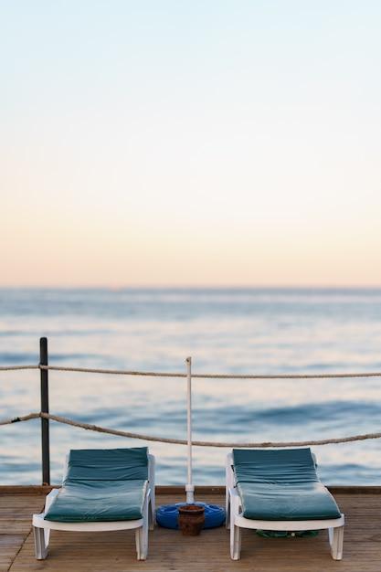 Две пустые кровати на деревянном пирсе красивым спокойным утром. туристическая пристань в морском заливе Бесплатные Фотографии