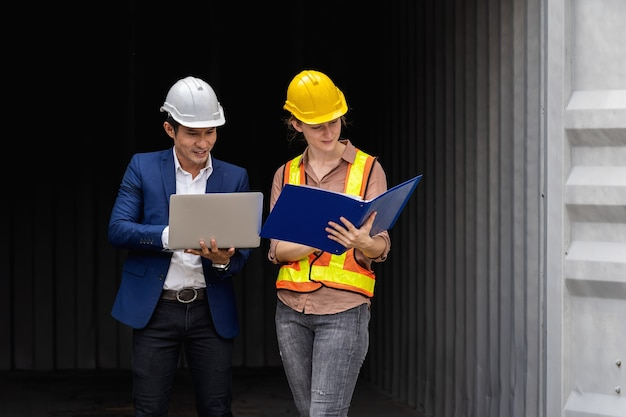 Two engineer worker hold a laptop, document for checking a quality of containers box from cargo ship for export and import, blue container background Premium Photo