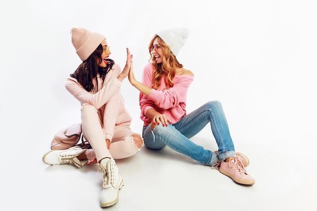 Due donne entusiaste in un bel vestito invernale rosa, cappelli rosa e maglioni che si rilassano sul pavimento, divertendosi su sfondo bianco. Foto Gratuite
