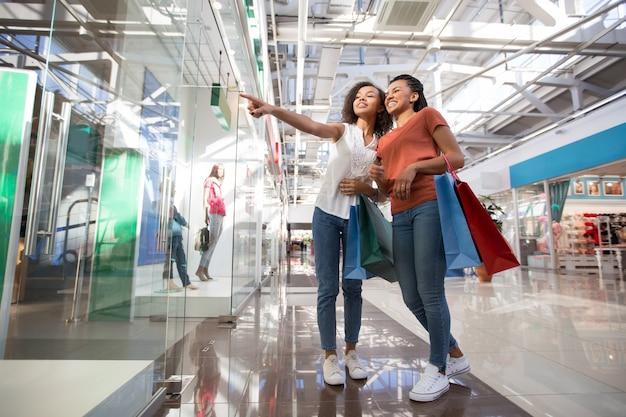 Две возбужденные черные девушки, указывающие на окно магазина Бесплатные Фотографии