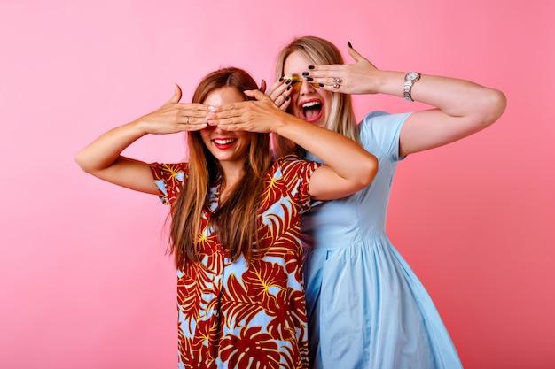 Две возбужденные женщины улыбаются и закрывают глаза руками, в ярких платьях Бесплатные Фотографии