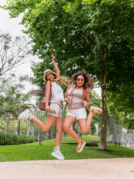 Two excited young women holding map and camera in hand jumping in the air Free Photo