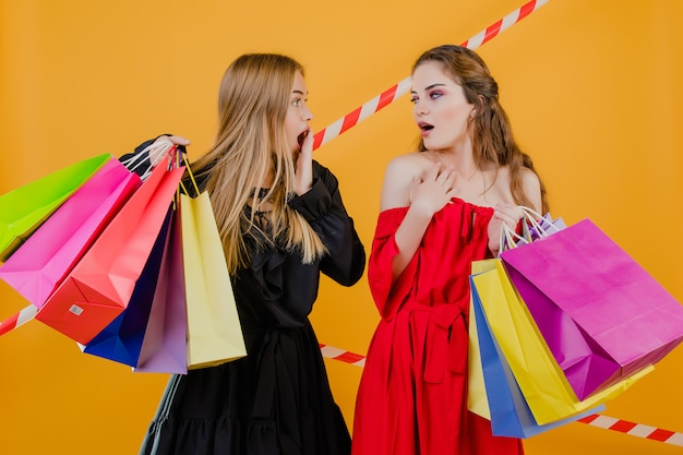 Two excited young women with colorful shopping bags and signal tape isolated over yellow Premium Photo