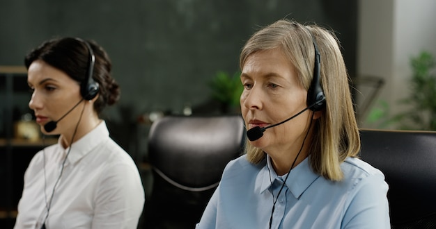 Two female call center workers sitting at table, typing on keyboards of computers and talking with clients in headset. Premium Photo