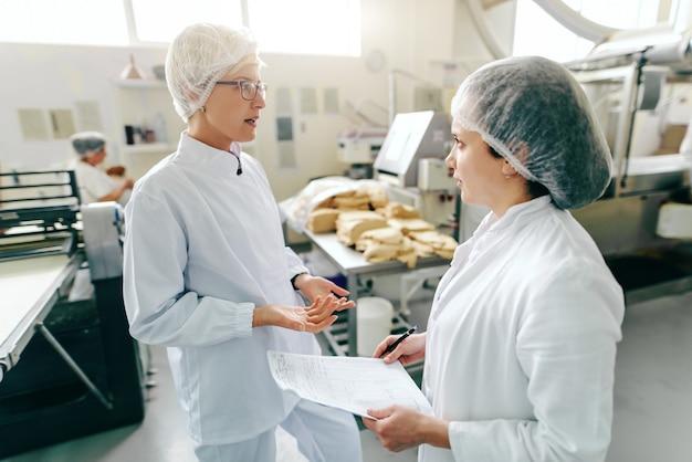 2 женских кавказских работника говоря о работе пока стоящ в фабрике еды. один из них держит документы. в фоновом режиме машины. Premium Фотографии