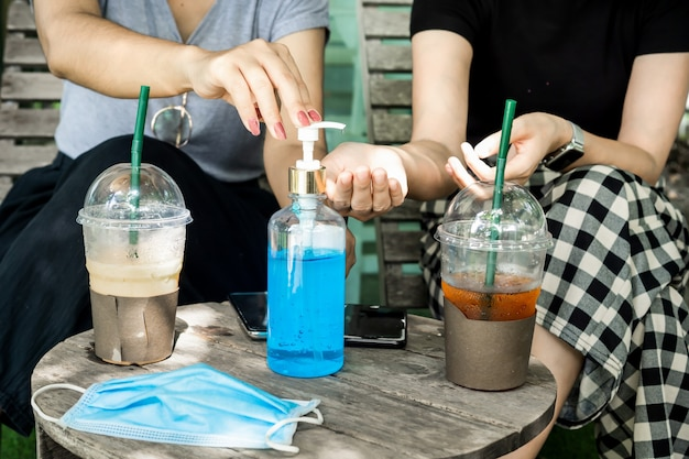 Two female cleaning their hands  with alcohol gel at coffee shop Premium Photo