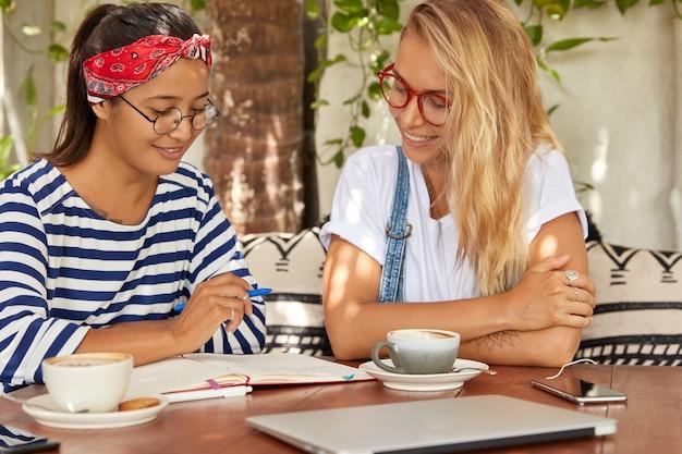 2人の女性の同僚が互いに話し、メモ帳でメモを取り、芳香のあるコーヒーを飲みます 無料写真