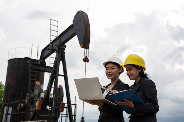 Two female engineers stand beside working oil pumps with a white sky . Free Photo