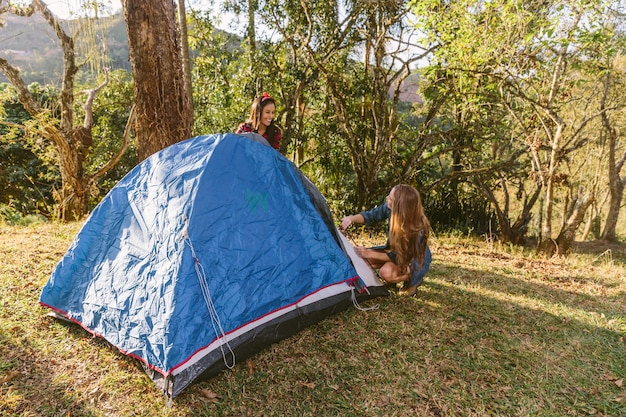 Two female friend setting tent while camping in forest Free Photo