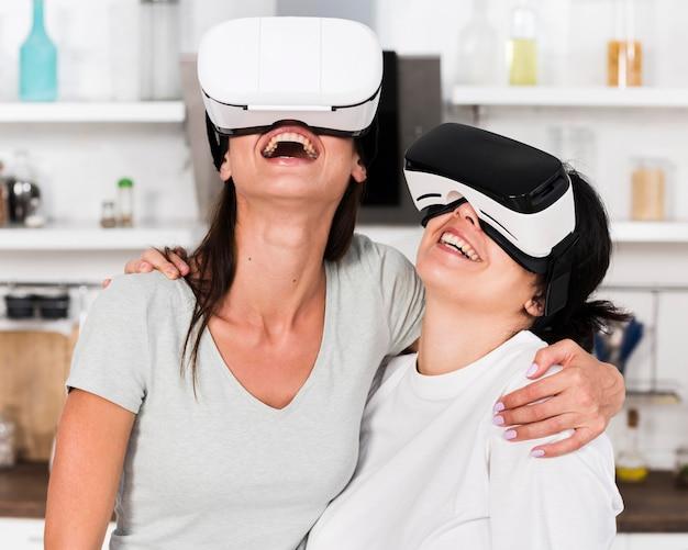 自宅で仮想現実のヘッドセットを楽しんでいる2人の女性の友人 無料写真