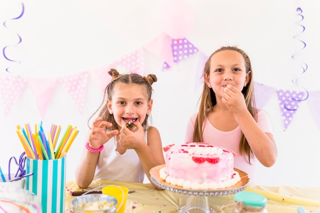 Two female friends eating cake while enjoying in birthday party Free Photo
