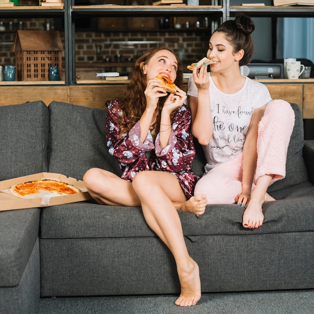 Two female friends eating pizza at home Free Photo