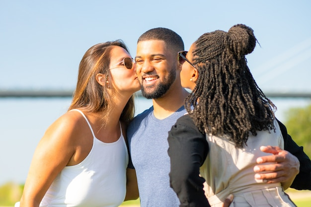 Two female friends kissing african american man on meadow. three friends spending time together in park. friendship Free Photo