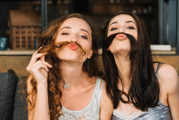 Two female friends making fake moustache with their hair Free Photo