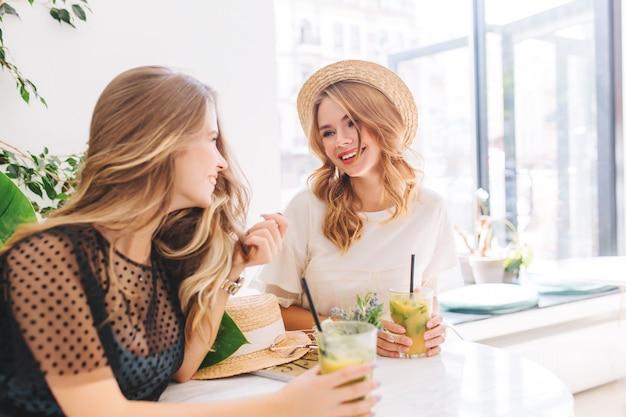お気に入りのカフェで一緒に休憩し、お互いに会えて嬉しいニュースを共有する2人の女性の友人 無料写真