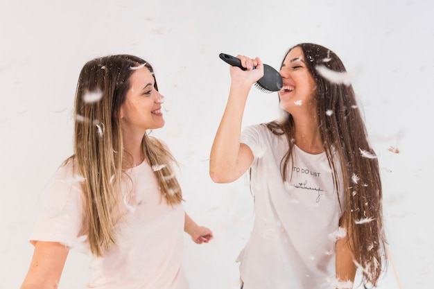 Two female friends sing song and making fun with feathers in air Free Photo