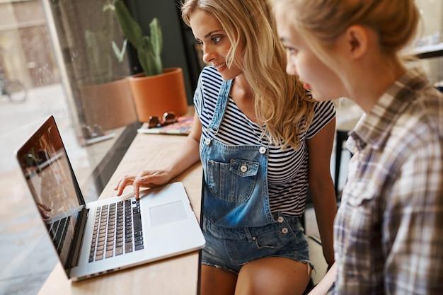 Due amici femminili che si siedono all'interno del caffè e che hanno caffè Foto Gratuite