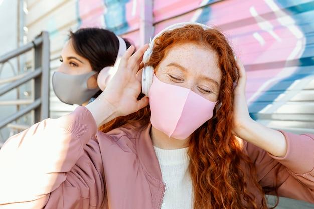 Due amiche con maschere facciali all'aperto ascoltando musica in cuffia Foto Gratuite