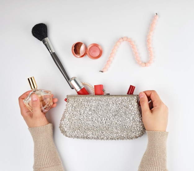 Two female hands and a silver cosmetic bag with cosmetics Premium Photo