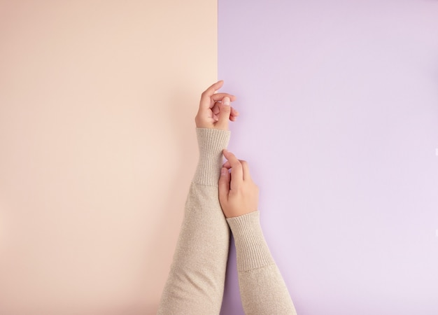 Two female hands with light smooth skin on a green pink background Premium Photo