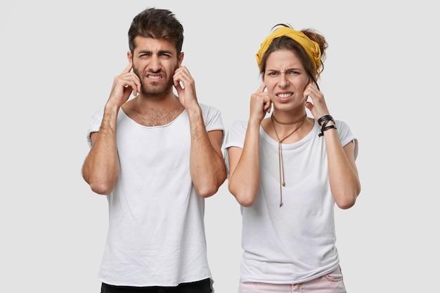 Due adulti maschi e femmine si accigliano, tappano le orecchie mentre sentono qualcosa di spiacevole, indossano abiti casual, isolati su un muro bianco, ignorano il suono fastidioso Foto Gratuite