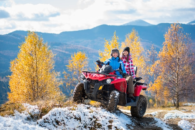 Two female riders atv in jackets and hats on a snow-covered trail at sunny autumn day against trees with yellow leaves and mountains Premium Photo