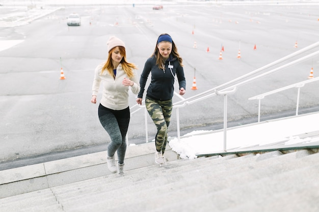 Two female runner jogging on the staircase in the winter Free Photo