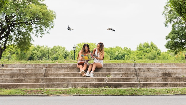 Two female tourist sitting on staircase viewing map in the park Free Photo