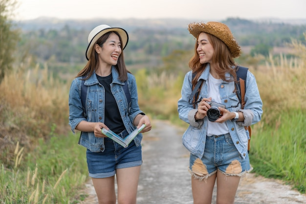 Two female tourist with backpack in countryside Premium Photo