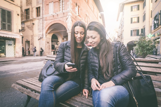 Two female twins looking at a smart phone Premium Photo