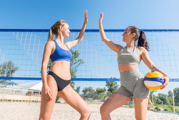 2人の女子バレーボール選手がネットの前でハイファイブ 無料写真