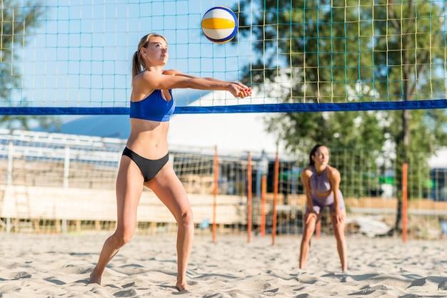 Due giocatori di pallavolo femminile che giocano sulla spiaggia Foto Gratuite