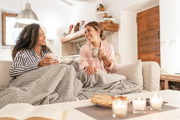 Две прекрасные молодые женщины сидят на диване с одеялом на ногах и смеются, наслаждаясь дома зимой, пьют чай с выпечкой - домашний образ жизни пары женщин-смешанных рас Premium Фотографии