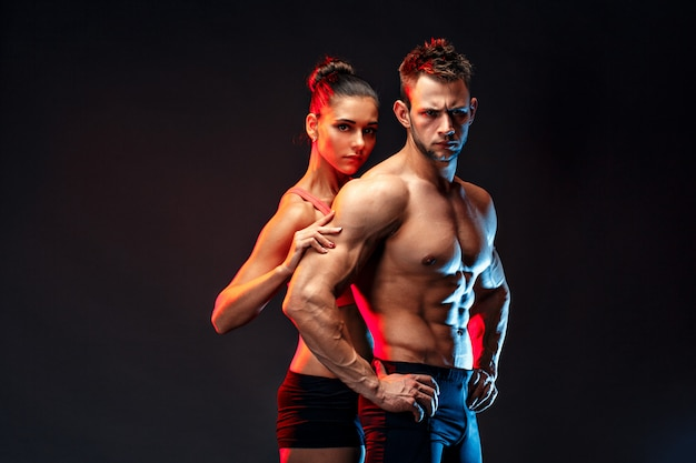Two fit sportspeople posing together, close to each other. Premium Photo