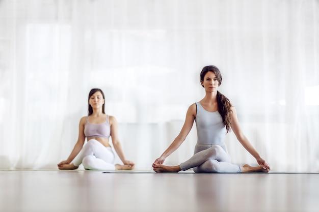Two focused attractive caucasian girls in knee pile position. yoga studio interior. Premium Photo