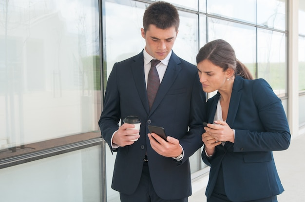 Two focused colleagues with phones sharing information Free Photo
