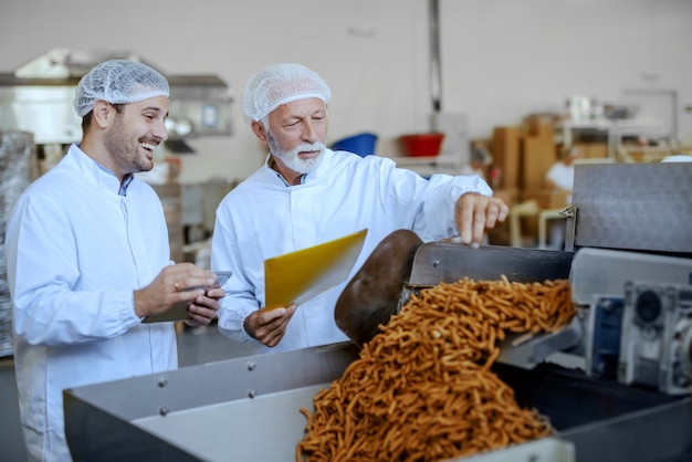 Two focused inspectors in white uniforms and hairnets evaluating quality of food. both are dressed in white uniforms and having hairnets. food plant interior. Premium Photo
