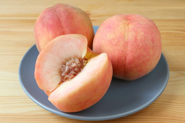 Two fresh ripe peach whole fruits and one cut peach on a blue plate served on wooden table. Premium Photo
