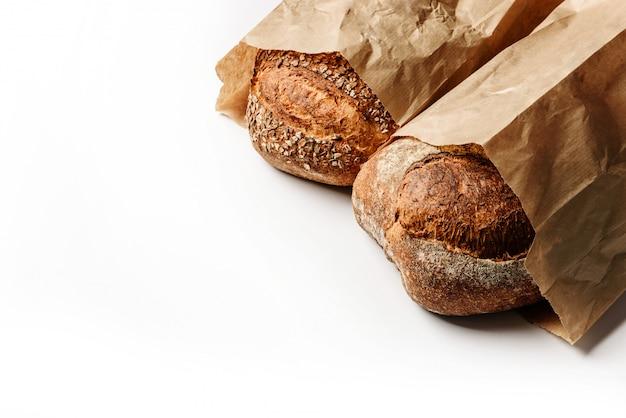 Два свежих деревенских хлеба в ремесленных сумках Premium Фотографии