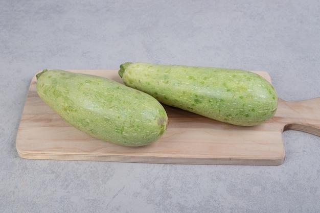 木の板に2つの新鮮なズッキーニ。高品質の写真 無料写真