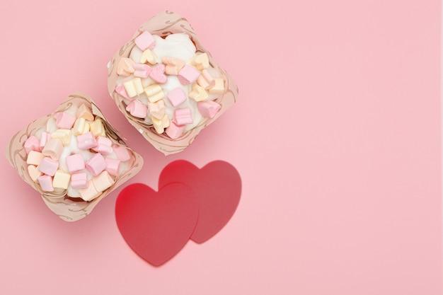 甘いアイシングとハート型のマシュマロで覆われた焼きたてのカップケーキ2つと、ピンクの背景に赤いハート2つ。テキストの場所。バレンタイン・デー Premium写真