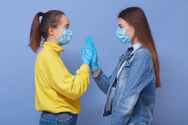 Двое друзей носят повседневную одежду, медицинские маски и латексные перчатки Бесплатные Фотографии