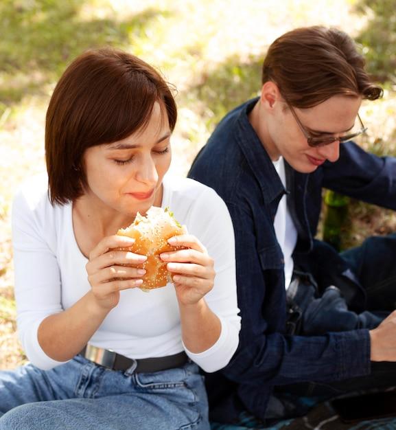 公園でハンバーガーを食べている2人の友人 無料写真