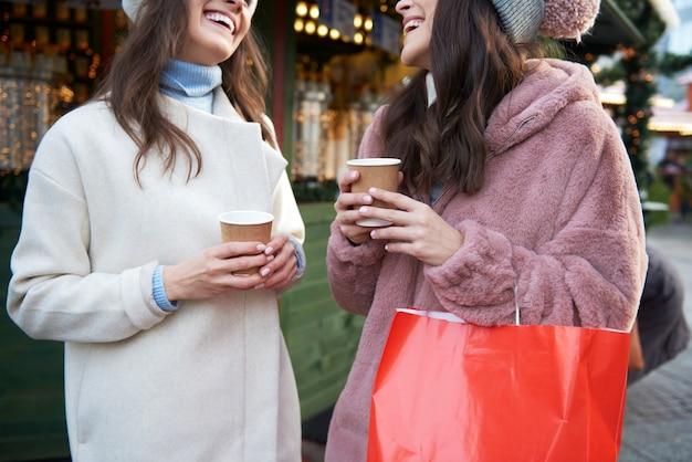 クリスマスマーケットでおしゃべりしてワインを飲む2人の友人 無料写真