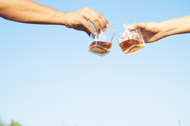 Two friends clink glasses of whisky drink alcoholic beverage together on blue sky background Premium Photo