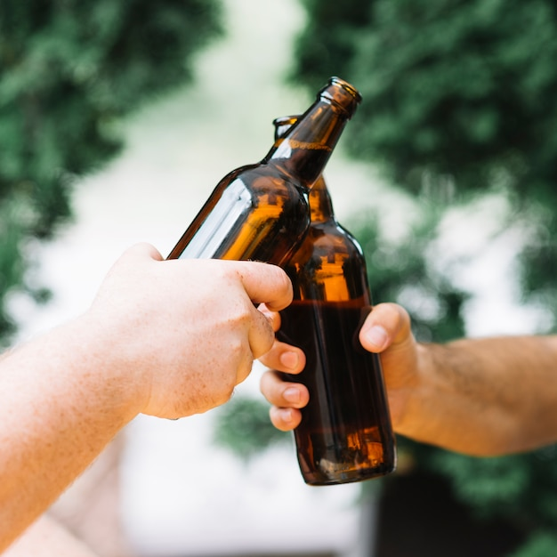 Two friends clinking the bottles of beer at outdoors Free Photo