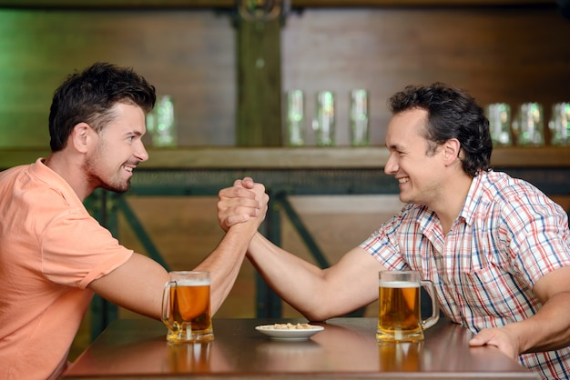 Two friends drinking beer and having fun at the pub. Premium Photo