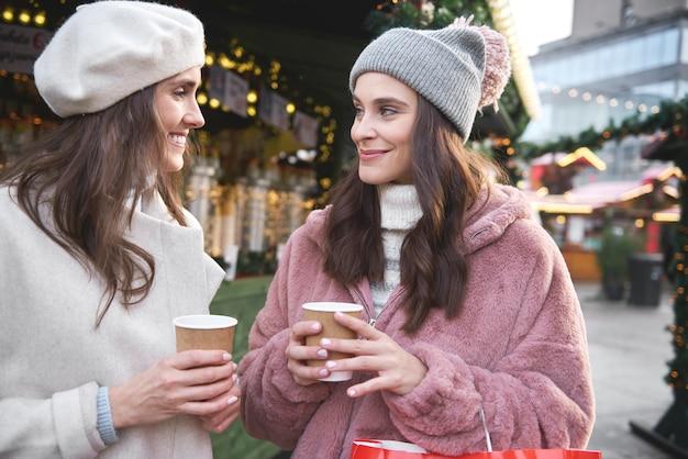 ホットワインを飲むクリスマスマーケットの2人の友人 無料写真